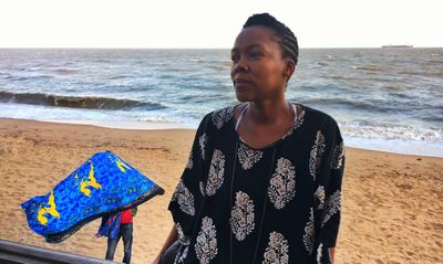 Journalist Nikiwe Bikitsha on the sands of Mozambique, with a ship and a hawker in the background. Two strands of the country's economy.